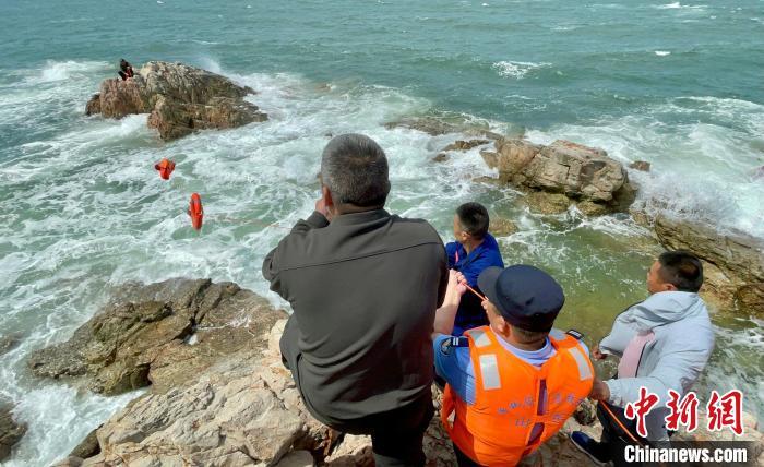 救援人员采用鱼竿甩线的方式将救生衣、救生绳等救援物资传到被困游客手中。 张亦凡 摄